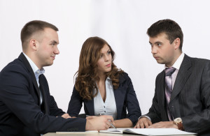 Three business people discuss the deal