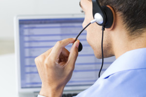 man wearing headset looking at monitor